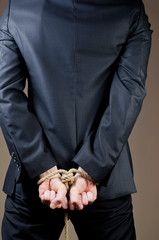 man in suit with tied hands