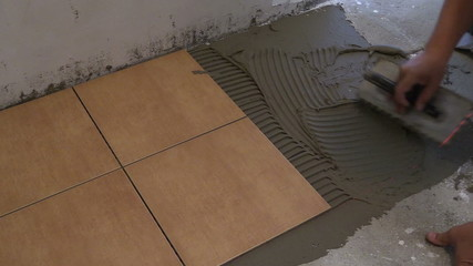 master hand puts tile cement glue on floor. Home renovation