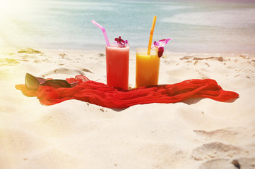 Pair of fruit shakes, red shawl and sunglasses on the beach of P