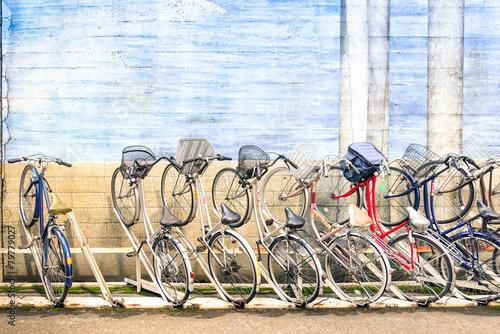 Multicolored vintage bicycles in metal rack in Tokyo city