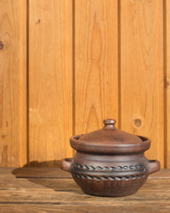 Clay pot with pattern on wooden boards