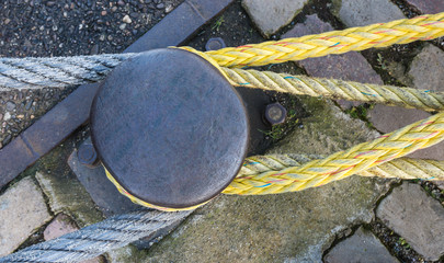 Top view of an iron bollard with ropes