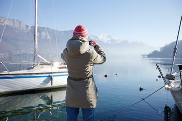 Woman taking picture of mountain lake