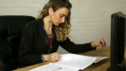 atrtactive female italian spanish executive looking at paperwork