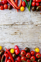 Frame of tomatoes and paper on wooden background