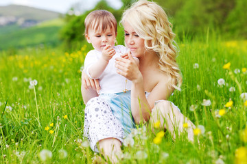 young woman playing with her child in flowers field