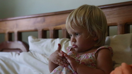 little blonde girl lies in the bed among toys and watches cartoo