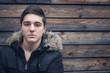 Ernst blickender Jugendlicher vor Holzwand
