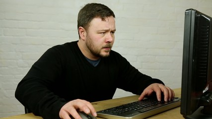 confused angry man typing in front of computer