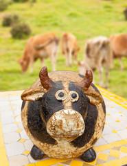 vache bibelot sur fond de vaches à la campagne
