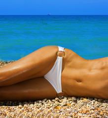 A woman sunbathes on a beach