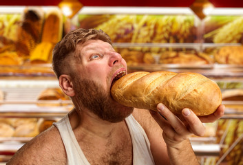 Man eating bread in the shop
