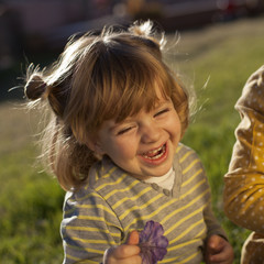 Niña pelirroja sonriendo con flor en la mano