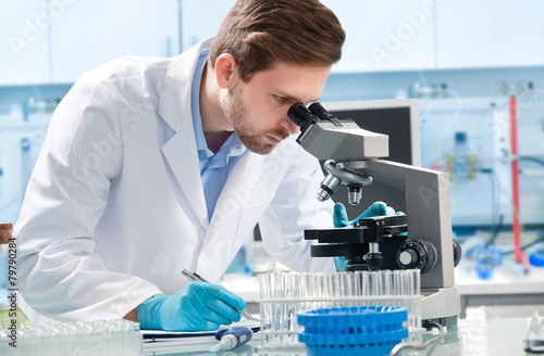 Scientist looking through a microscope in a laboratory - 79790284