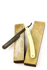 Old rusty  razor and two sharpening stones on a white background