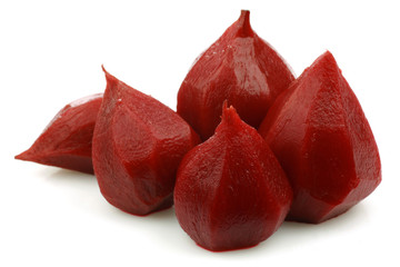 cooked and peeled red beetroots on a white background