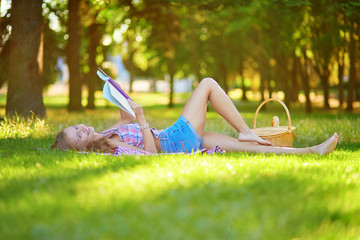 Girl lying on the grass and reading