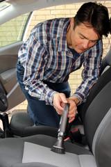 Autobesitzer reinigt seine Sitze mit  Bürstensauger