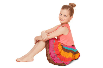 Little happy girl in colorful skirt sits, isolated on white