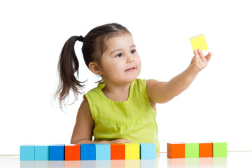 child plays with building blocks and learning of colors