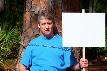 Environmentalist protesting deforestation with blank sign