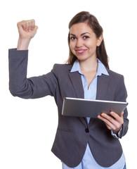 Junbelnde Geschäftsfrau im grauen Blazer mit Tablet