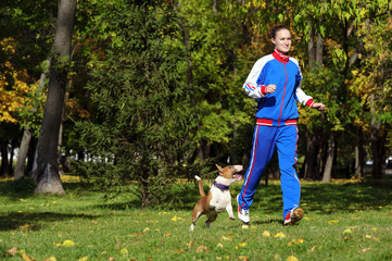 Young attractive sport girl jogging with dog in sunny park