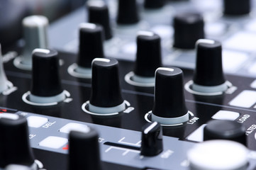 Fader and buttons of DJ mixer controller in nightclub