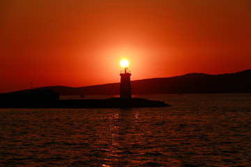 Lighthouse silhouetted against a sunset.