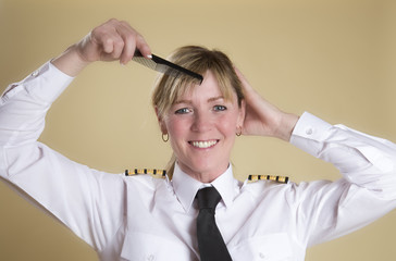 Attractive airline pilot combing her hair