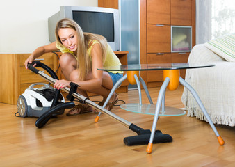 Blonde woman with vacuum cleaner