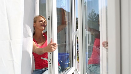 Pretty, young woman doing house works, washing windows
