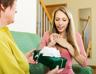 Mature mother presenting gift in box to happy daughter