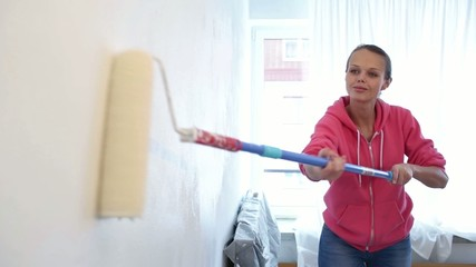 Home reconstruction: young woman painting wall in her apartment