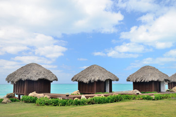 Bungalows in front of turquoise sea.