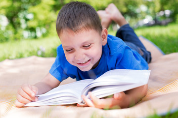 Boy lying on picnic and reading book
