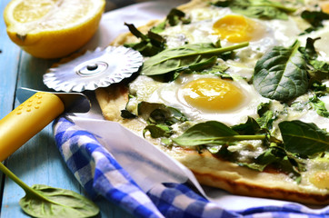 Pizza with spinach and fried eggs.