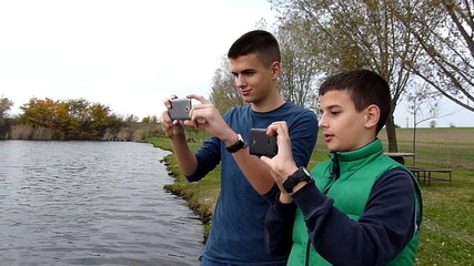 Two boys taking photos with their smart phones on lake shore