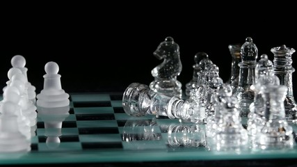 Glassy chess is placed on black background. Slow motion