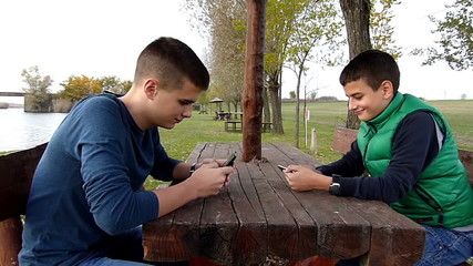 Two boys having fun with their smart phones on lake shore
