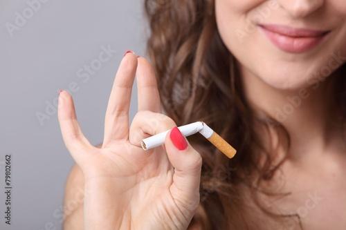 Frau hält durchgebrochene Zigarette - 79802662