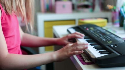 Cute little school girl playing an electric piano