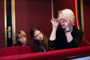Mother with kids watching theater performance