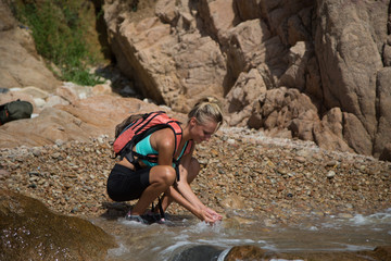 Adventure girl wash her face in the wild river