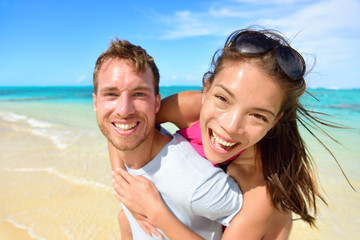 Young couple having fun laughing on beach holidays