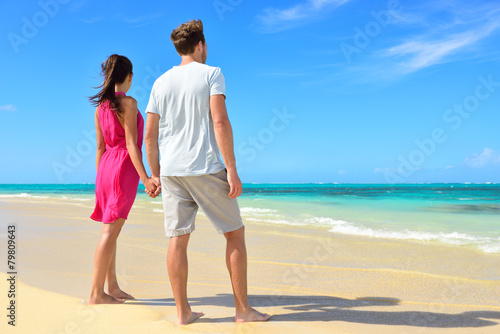 Beach couple looking at ocean view from behind - 79809643