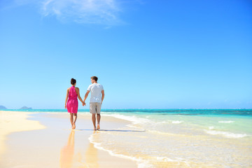 Beach couple holding hands walking on honeymoon