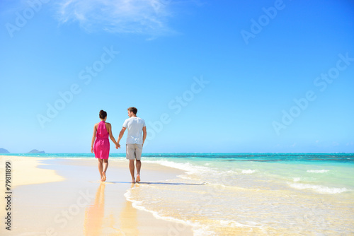 Beach couple holding hands walking on honeymoon - 79811899