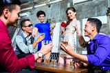 Asian friends drinking cocktails in nightclub