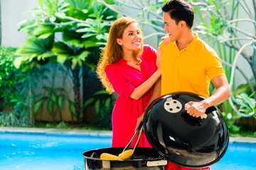 Asian couple having barbecue at the pool